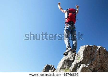 Climber reaches his arms up, standing on a stone at the top of his route, over a deep blue sky. - stock photo