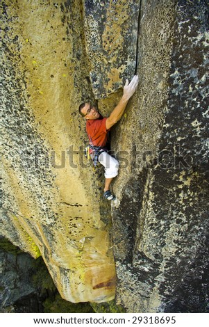 Climber reaching for his next hold on a steep cliff in Sequoia National Park, California. - stock photo