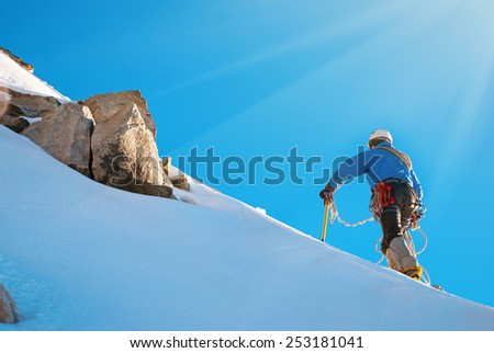 Climber reaching the summit of mountain - stock photo