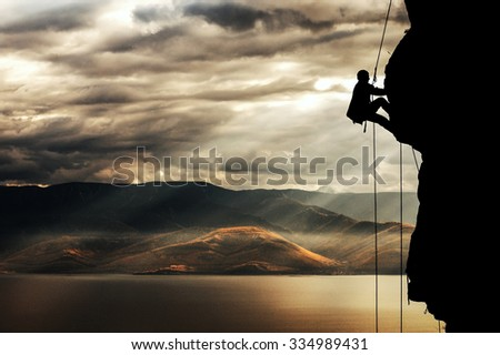 Climber rises on a cliff on the shores of Lake Baikal.