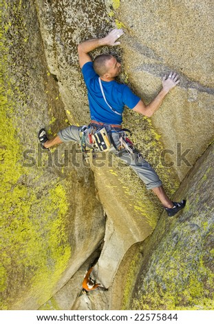 Climber searches for  handholds as he stretches between two rock walls, Sequoia National Monument, California. - stock photo