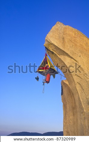 Climber sets up his hanging camp on an overhanging, sheer rock pinnacle.