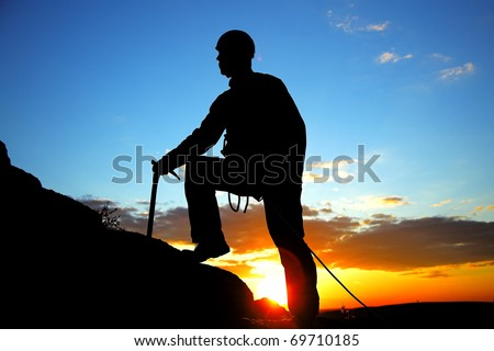 climber silhouette against cloudy sunset - stock photo