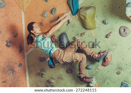 Climber sporty girl climbing on practice wall indoor - stock photo