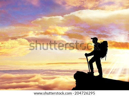 climber standing a mountain on sunset background. - stock photo