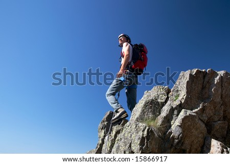 Climber standing on a stone at the top of his route, over a deep blue sky. - stock photo