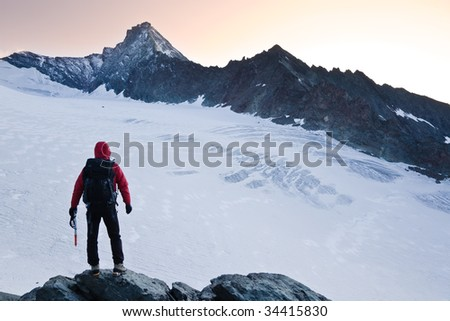Climber stands in front the glacier and the peak of Mt Grivola, Gran Paradiso National Park, Italy.
