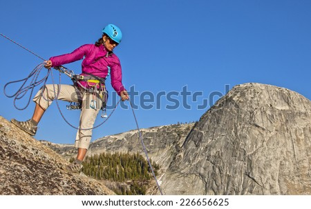 Climber struggles for her next grip on the edge of a challenging cliff. - stock photo