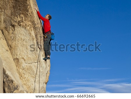 Climber struggles for his next grip on a steep rock wall.