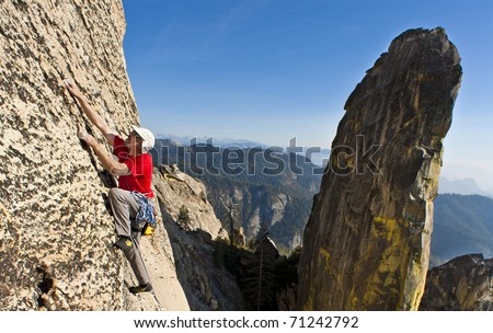 Climber struggles for his next grip on a steep rock wall. - stock photo