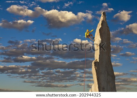 Climber struggles for his next grip on the edge of a challenging cliff. - stock photo