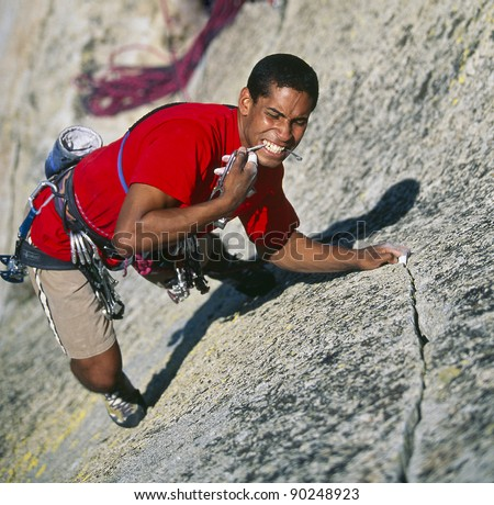 Climber struggles to cling to the edge of a challenging overhang. - stock photo
