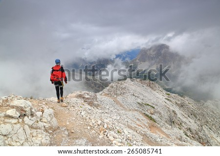 Climber  surrounded by clouds on a mountain top, Dolomite Alps, Italy - stock photo