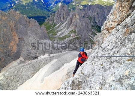 "Climber traversing high above ground along the steel cable of via ferrata ""Merlone"" in Cadini di Misurina, Dolomite Alps, Italy - stock photo"