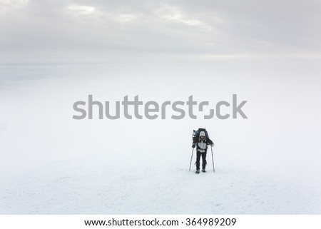 Climber walking on a mountain in bad weather winter