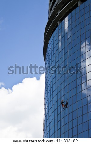 climber washes windows of office center - stock photo