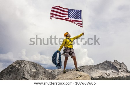 Climber waves an American Flag from the summit after a challenging ascent. - stock photo