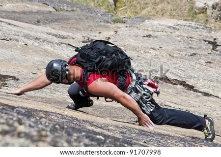 climber while climbing a vertical rock wall - stock photo