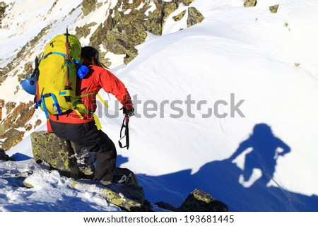 Climber with an ice axe descends the mountain in sunny winter day