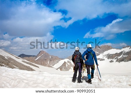 Climber with climbing equipment on the top of the snowy mountain looks into the distance - stock photo