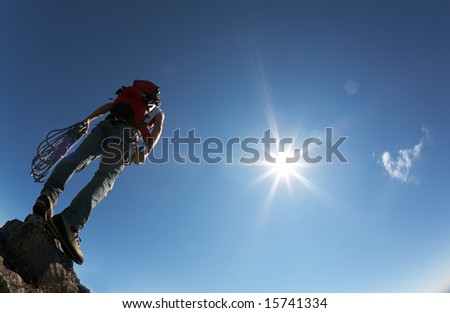 Climber, with climbing gears, standing on a stone at the top of his route, over a deep blue sky. - stock photo
