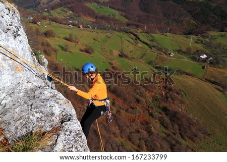 Climber woman abseiling on vertical rock, high above ground - stock photo