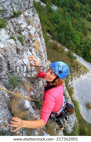 Climber woman ascending a steep wall high above ground - stock photo
