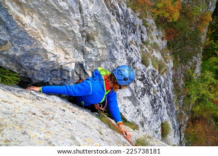 Climber woman finding balance on steep limestone route - stock photo