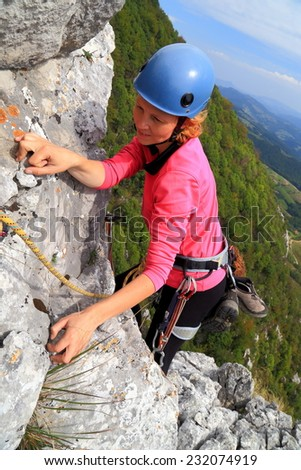 Climber woman grabs a handhold on aerial rock ridge  - stock photo