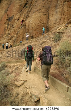 Climbers approaching rock face with backpacks,		Smith Rock State Park, 	Central Oregon