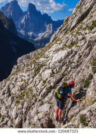 climbers are ascending the mountain via ferrata, Italy, Dolomites - stock photo
