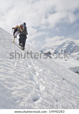 Climbers ascending a snow slope on Mount Rainier's Kautz Glacier. - stock photo