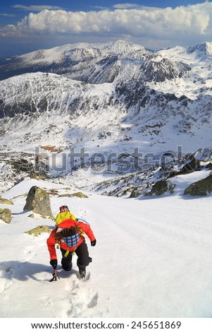 Climbers ascending a steep slope above snow covered mountains - stock photo