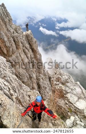 "Climbers ascending via ferrata ""Punta Ana"" high above clouds, Tofana massif, Dolomite Alps, Italy - stock photo"