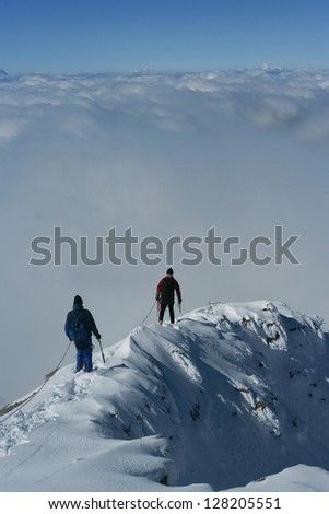 Climbers at snowy ridge above clouds - stock photo