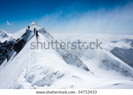 Climbers balancing in blizzard on a narrow ridge of Lyskamm (aka Maneater, 4480 m) - stock photo