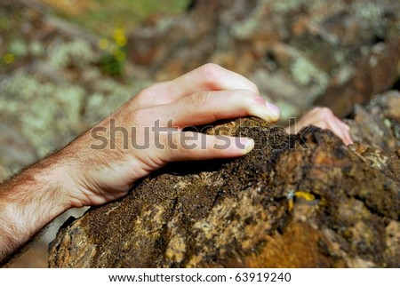 Climbers hands  fixing on the edge of a cliff - stock photo