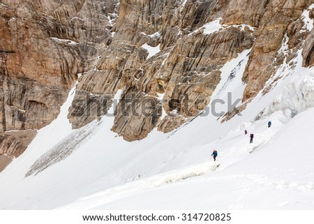 Climbers Linked with Protection Rope Ascending Glacier Members of Alpine Expedition Walking Up on Steep Snowfield Dangerous Crevasses Rope Belay Steep Rock Wall on Background - stock photo