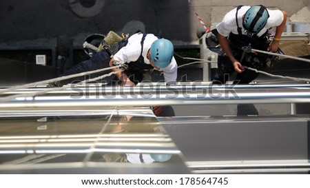 Climbers on Office Building. Workers hanging on climbing ropes and working together.  - stock photo