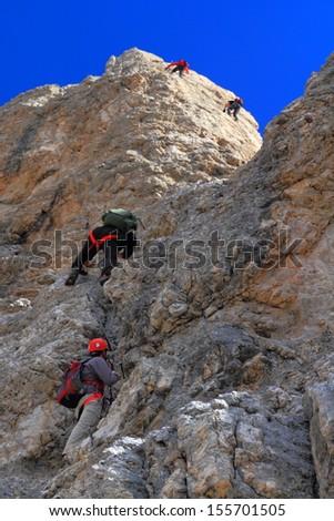 Climbers on steep via ferrata route, Dolomite Alps, Italy - stock photo