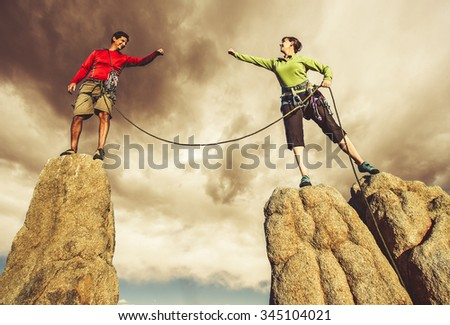 Climbers on the edge of a challenging cliff at sunset. - stock photo