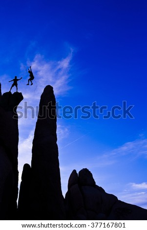 Climbers on the edge of a challenging cliff at sunset.