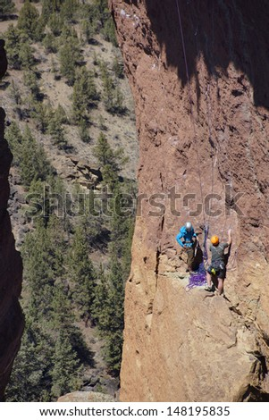 Climbers on  the overhanging cliff of Monkey Face, one iof the premier climbs in the Smith Rock area, Central Oregon  - stock photo