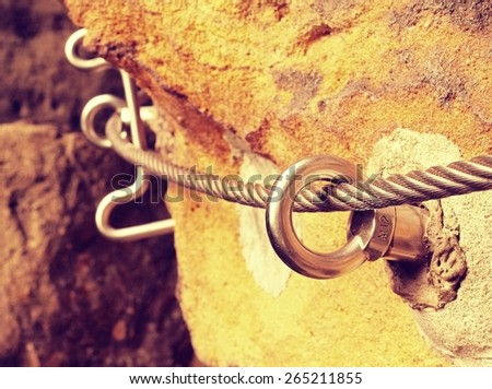 Climbers rope path. Iron twisted rope fixed in block by screws snap hooks. The rope end anchored into sandstone rock.  - stock photo
