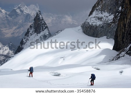 Climbers roped together in search of a way between crevices - stock photo