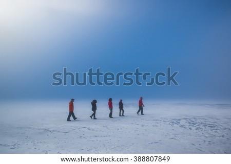 Climbers walking on the frozen lake - stock photo