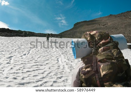 Climbers walking on top of mountain on snow. Back of backpacker - stock photo