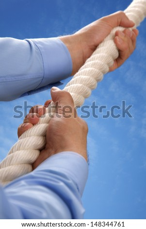 Climbing a rope upwards towards a blue sky concept for aspirations, growth and leadership - stock photo