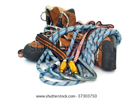 climbing and hiking gear - three carabiners, ropes and leather brown boots - stock photo