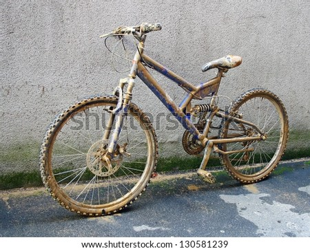 climbing bike completely covered with brown mud and sprinkles - stock photo